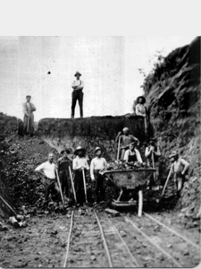 The men shown building what is now 240th Street had to cut down the height of the hills by shoveling out a notch for the road to travel through.