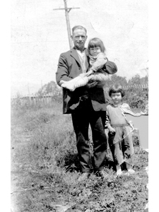 Joan Jones [standing] and sister Evelyn with neighbor Mr. England while they were living in a tent on the vacant lot that became the post office.