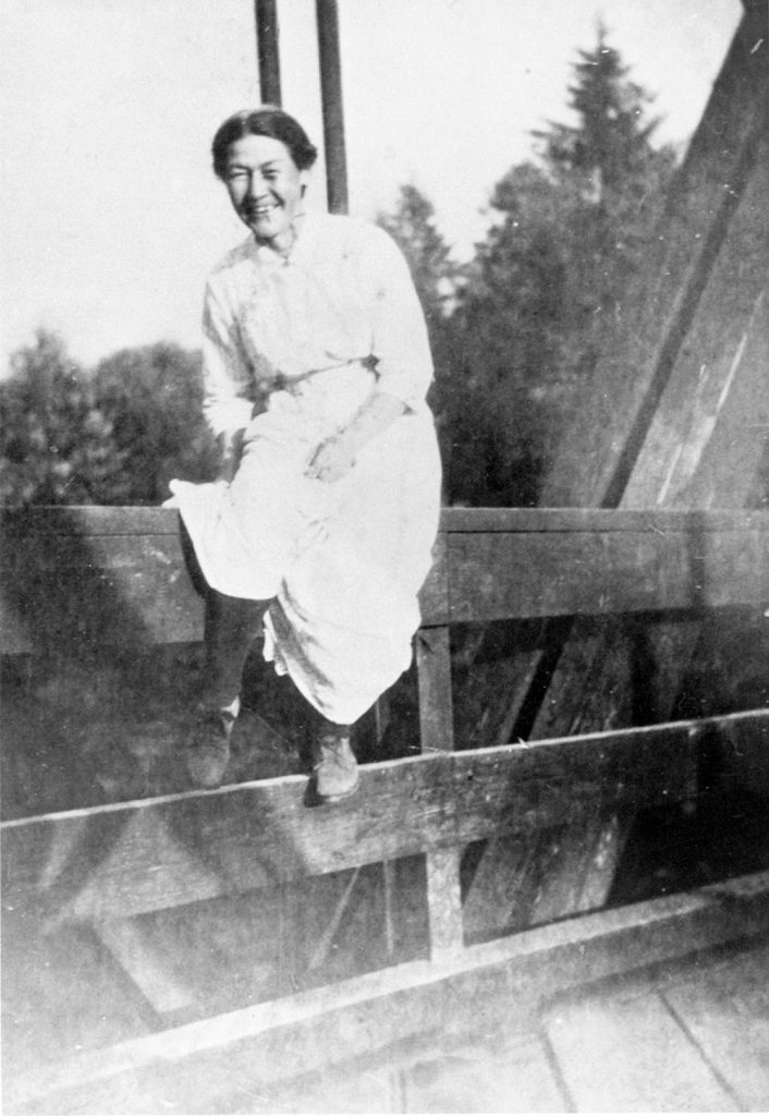 Susan Greenwell sitting on bridge over Alouette River in about 1915