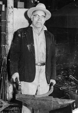 Sam Saari in 1969 working at his anvil with his forge behind him.