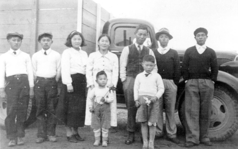 The Tsuyuki family.  From left:  Hiro, Taka, Yuriko, Tori with Roy in front, Tokutaru (Pop), Tad, Koo, and Jim.  They are posed in front of their farm truck at Albion.