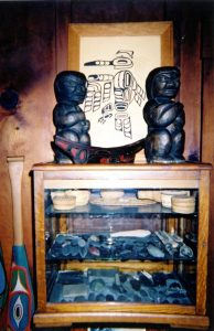 A living room display cabinet on the North wall in the Byrnes' home.  Shows carvings, canoe baskets and points.  This was taken before any items were removed.